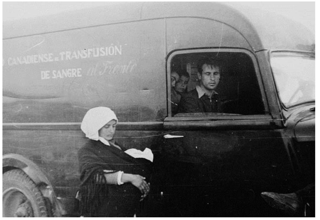 Refugees_beside_an_ambulance_of_the_Canadian_Blood_Transfusion_Unit