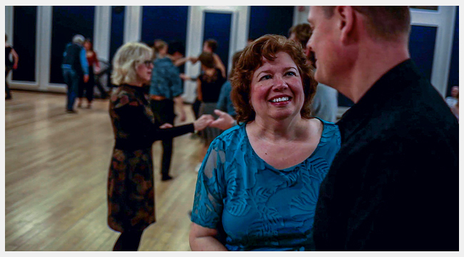 Image of Linda Paul dancing with a man in her dancing class with other couples dancing.