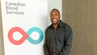 Image of Dujon Donaldson standing beside a Canadian Blood Services banner stand