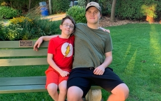 Nolan Clark sits on a park bench with his arm around his younger brother Nicholas Clark. Nolan donated blood for the first time after Nicholas had blood transfusions as an infant.