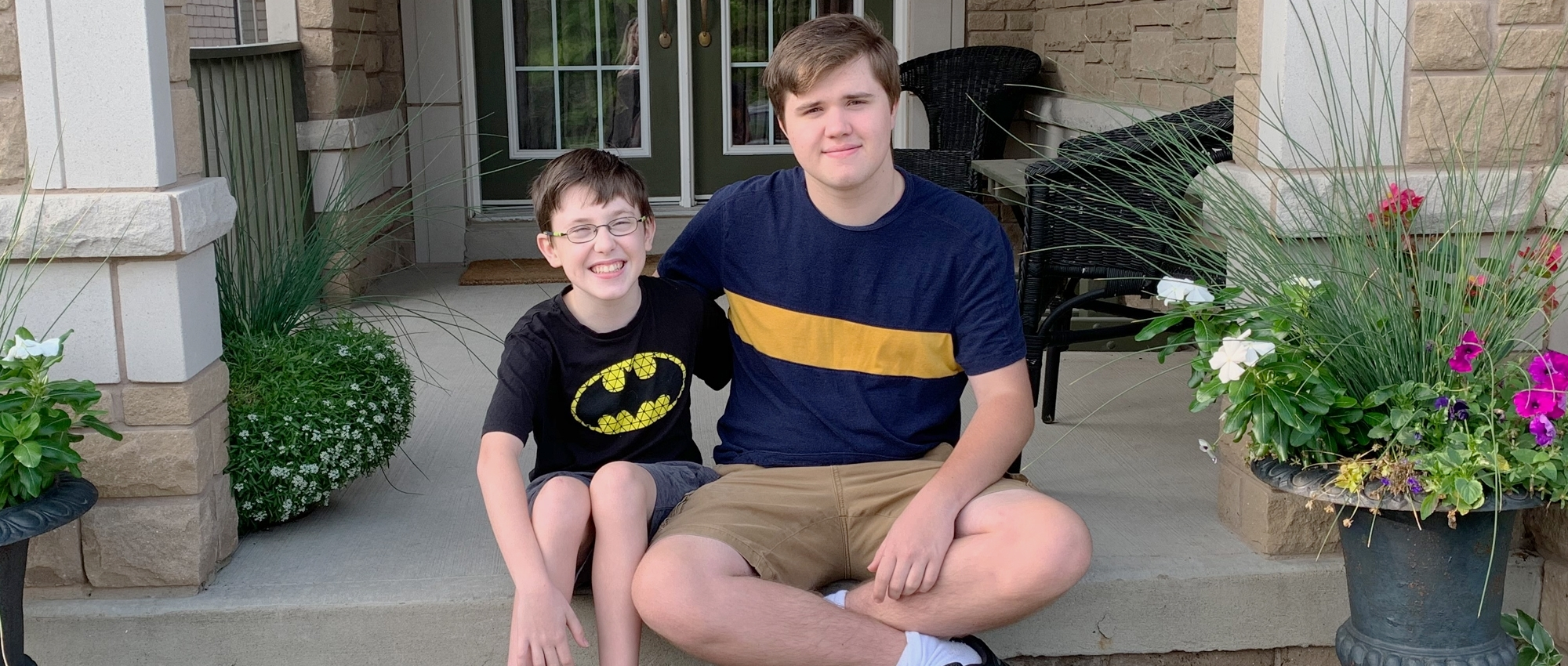 Nolan Clark, a teen who donated blood for the first time, sits on a porch with his younger brother Nicholas who had blood transfusions as an infant.