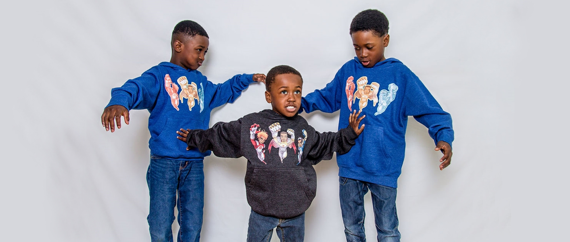 Hezekiah, Joiakim and Micah Felix pose in shirts that display the superhero characters in the book The Battle of Ottogatz.