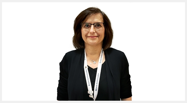 A woman with short brown hair and glasses wearing a Canadian Blood Services Brand Ambassador lanyard around her neck.