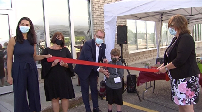 Image of Vice President of Plasma Jean-Paul Bédard and Heydan Morrison holding a pair of large scissors cutting the ribbon for the temporary opening of Sudbury Plasma Centre