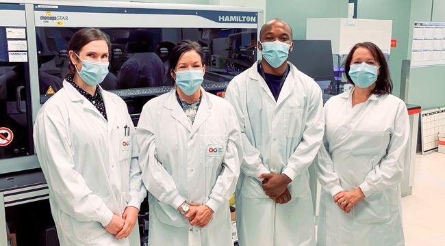 Thumbnail image of lab team members Stacey Vitali, Carissa Kohnen, Andy Tshiula Kalenga and Valerie Conrod standing together in front of a Hamilton machine wearing masks.